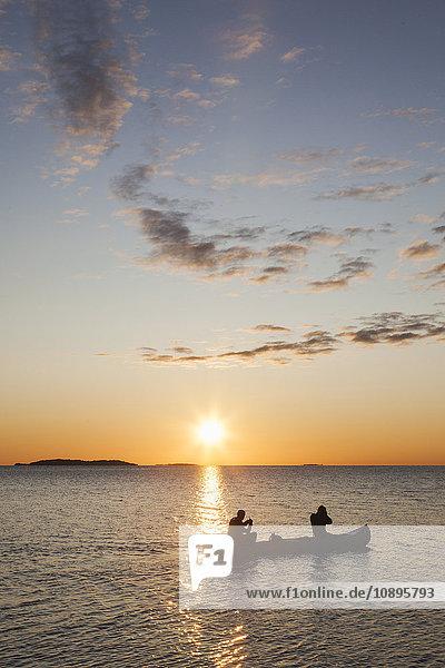 Schweden  Medelpad  Sundsvall  Alnon  Zwei Männer im Kanu auf der Ostsee bei Sonnenuntergang