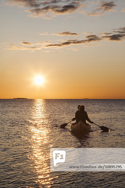 Schweden  Medelpad  Sundsvall  Essvik  Brattberget  Zwei Männer im Kanu bei Sonnenuntergang