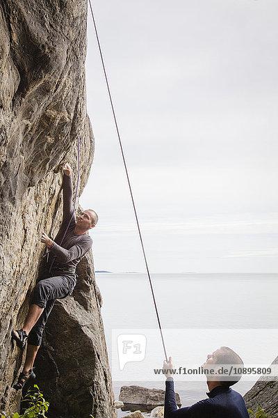 Schweden  Medelpad  Sundsvall  Essvik  Brattberget  Zwei Männer klettern Klippe