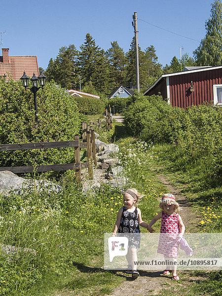 Schweden  Medelpad  Sundsvall  Mädchen (4-5)  die auf dem Land herumlaufen und Händchen halten