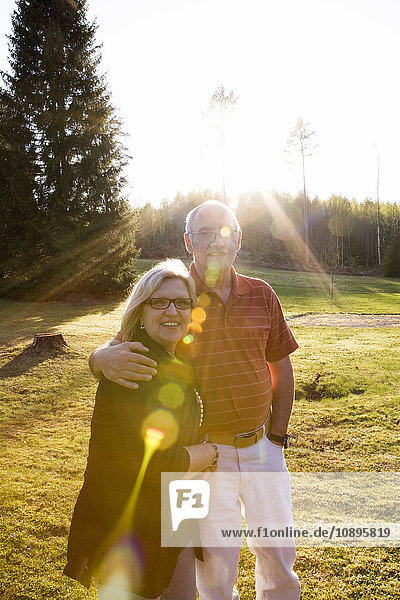 Schweden  Medelpad  Sundsvall  Mann und Frau stehen zusammen auf einer Wiese im Sonnenlicht.