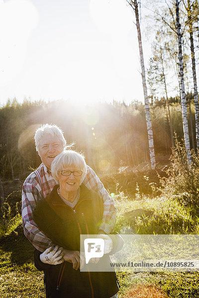 Schweden  Medelpad  Sundsvall  Seniorenpaar im Wald stehend umarmend