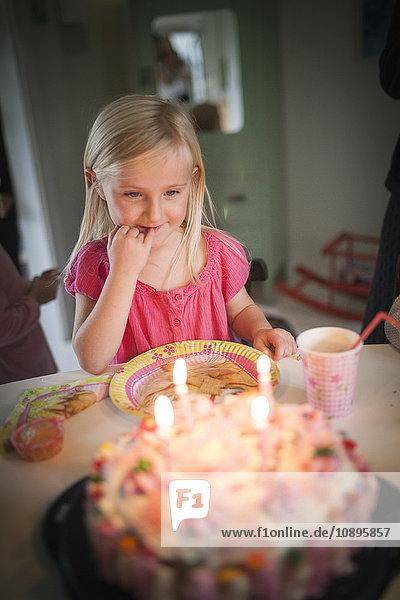 Schweden  Mädchen (4-5) beim Anblick des Geburtstagskuchens