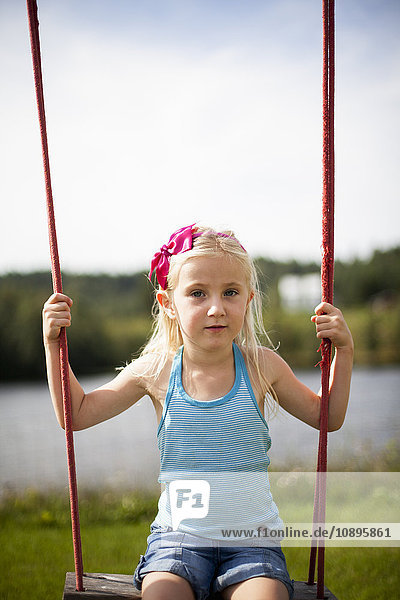 Schweden  Medelpad  Mädchen (6-7) sitzend auf Seilschaukel