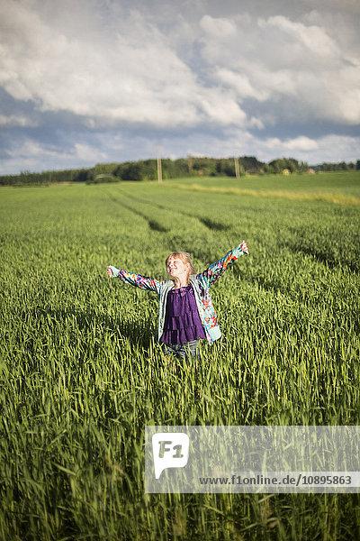 Schweden  Medelpad  Mädchen (8-9) stehend im landwirtschaftlichen Feld mit ausgestreckten Armen