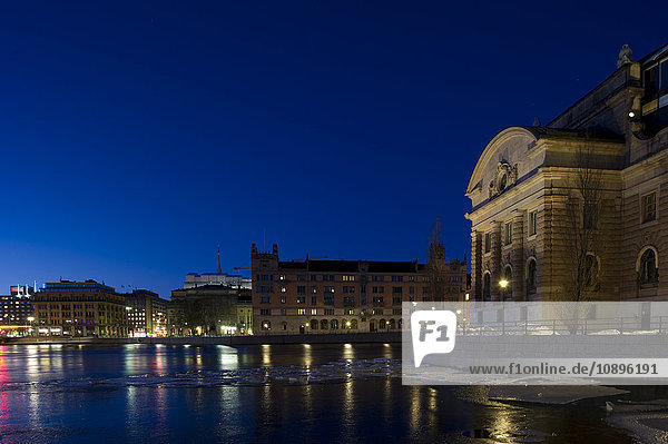 Stockholm  Schweden  Blick auf die Uferpromenade und das Parlamentsgebäude in der Abenddämmerung