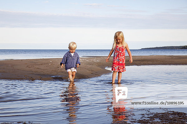 Schweden  Medelpad  Bergafjarden  Junge und Mädchen (4-5) beim Spielen im Wasser