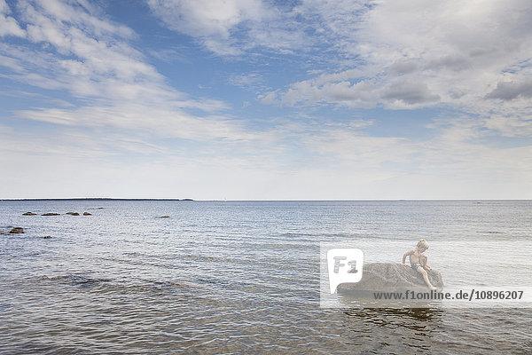 Schweden  Halsingland  Mellanfjarden  Junge (6-7) auf Felsen sitzend