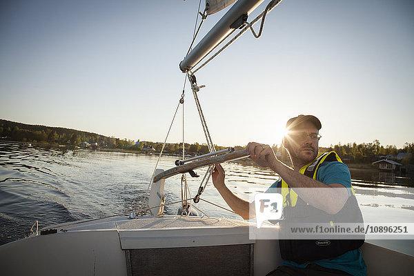 Schweden  Medelpad  Juniskar  reifer Mann bei Sonnenuntergang
