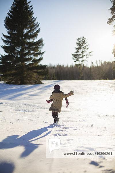 Schweden  Medelpad  Sundsvall  Girl (6-7) beim Wandern auf Schnee an sonnigen Tagen