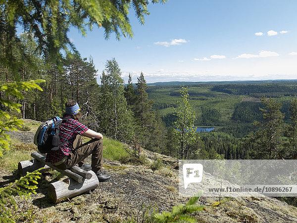 Schweden  Medelpad  Storberget naturreservat  Wanderer auf Holzbank im Wald sitzend und mit Blick auf die Aussicht