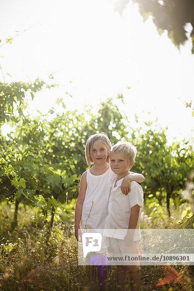 Italien  Toskana  Porträt der Schwester (6-7)  die den jüngeren Bruder (4-5) im Obstgarten umarmt.