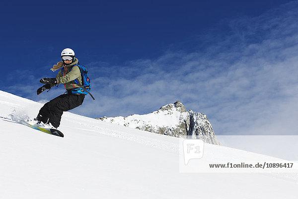 Schweiz  Andermatt  Junge Frau Snowboarden in den Alpen