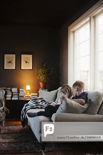 Denmark  Boy (8-9) and girl (4-5) sitting on sofa in living room