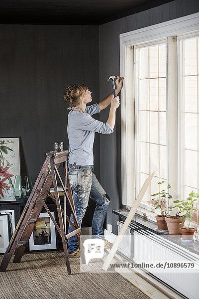 Schweden  Mittlere Erwachsene Frau hämmert Nagel im Wohnzimmer