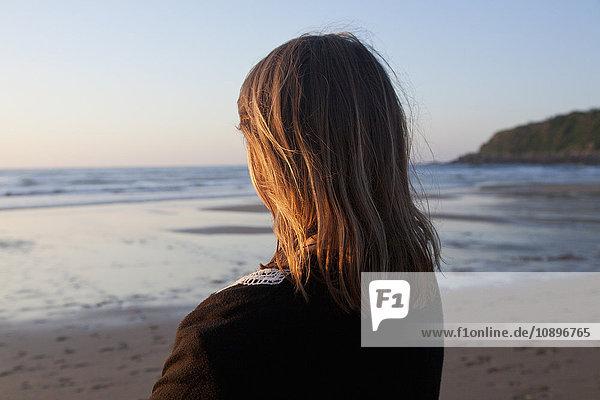 Spanien  Das Baskenland  Gipuzkoa  San Sebastian  Frau am Strand stehend und mit Blick auf den Golf von Biskaya bei Sonnenuntergang