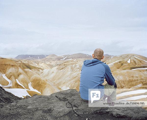 Island  Landmannalaugur  Mann auf dem Felsen sitzend und mit Blick auf die Aussicht