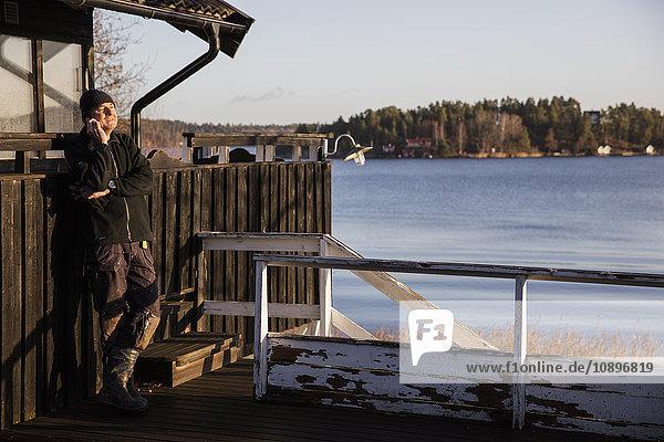 Schweden  Uppland  Stockholm Archipel  Rindo  Mann  der sich am Zaun lehnt und telefoniert