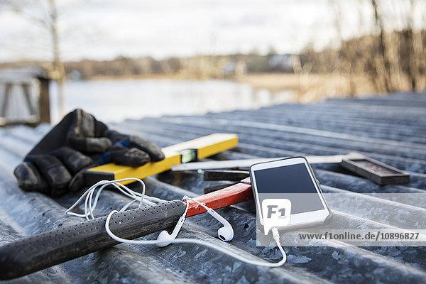 Schweden  Uppland  Rindo  Arbeitsgeräte und Smartphone auf Metalldach