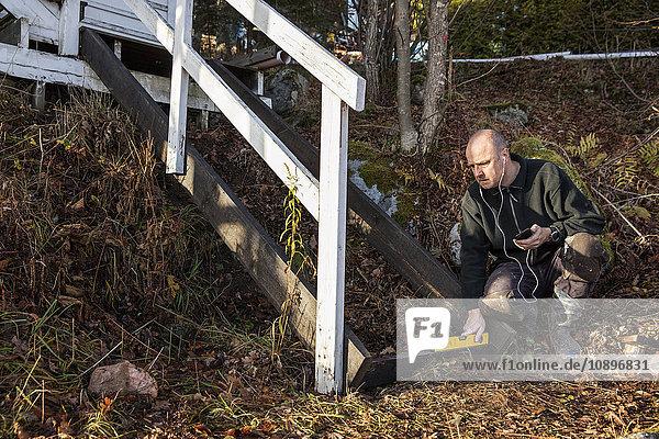 Schweden  Uppland  Rindo  Mann repariert Holztreppe