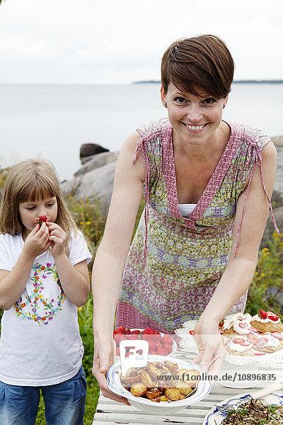 Schweden  Uppland  Roslagen  Frau bereitet Picknicktisch am Meer vor