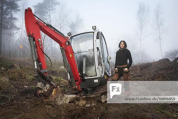 Schweden  Uppland  Nacka  Frau steht beim Bulldozer im Wald