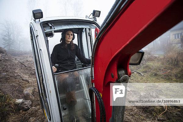 Schweden  Uppland  Nacka  Frau fährt Planierraupe