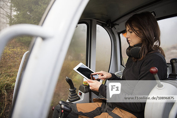 Schweden  Uppland  Nacka  Frau mit digitalem Tablett im Bulldozer