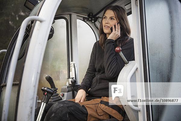 Schweden  Uppland  Nacka  Frau am Telefon im Bulldozer
