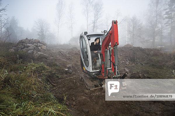 Schweden  Uppland  Nacka  Frau mit Telefon im Bulldozer