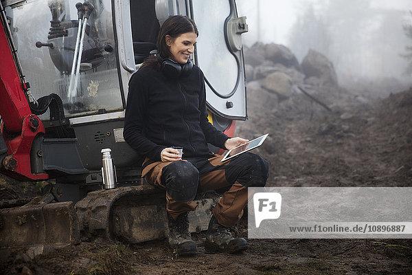 Schweden  Uppland  Nacka  Junge Arbeiterin sitzend mit dem Earth Mover und mit dem digitalen Tablett