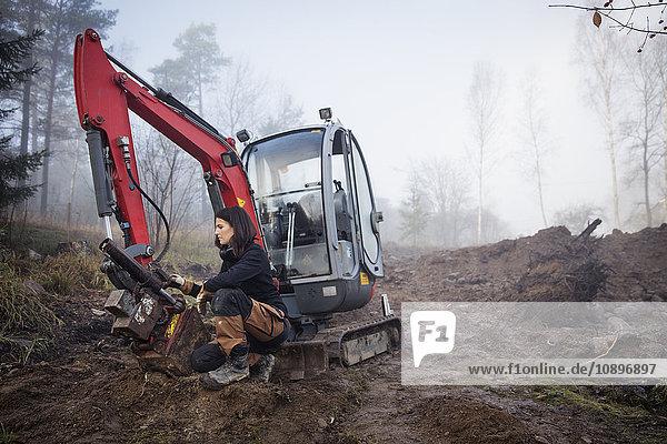 Schweden  Uppland  Nacka  Junge Arbeiterin im Nebel hockend