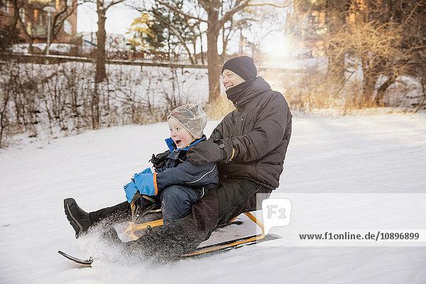 Schweden  Sodermanland  Johanneshov  Vater mit Sohn (4-5) Rodeln