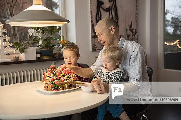 Schweden  Mann und zwei Jungen (18-23 Monate  4-5) dekorieren Lebkuchenhaus