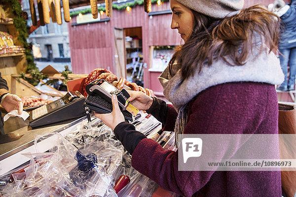 Schweden  Stockholm  Gamla Stan  Frau bezahlt mit Kreditkarte am Markt