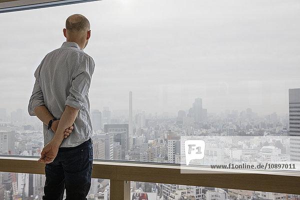 Japan  Tokio  Shibuya  Mann blickt durchs Fenster auf das Stadtbild