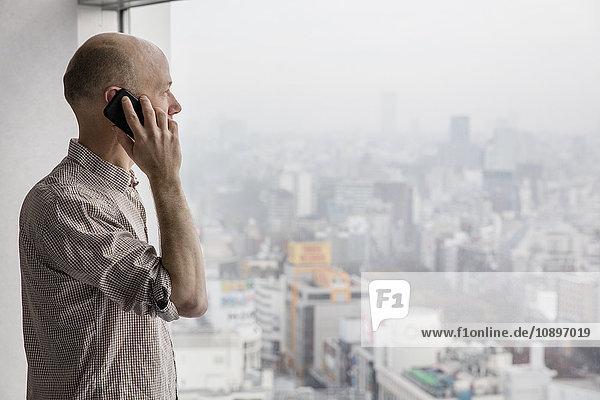 Japan  Tokio  Shibuya  Mann am Telefon und Blick durchs Fenster