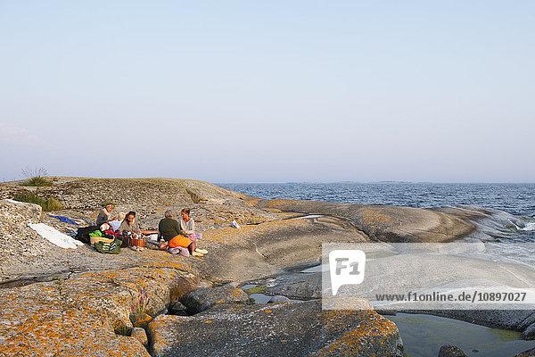Schweden  Stockholms Archipel  Sodermanland  Haninge  Norsten  Menschen beim Picknick auf Felsen am Meer