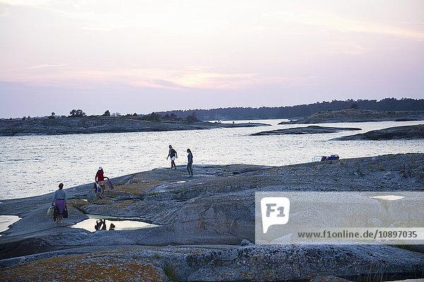 Schweden  Stockholms Skargard  Sodermanland  Varmdo  Villinge  Menschen  die auf Felsen am Meer spazieren gehen