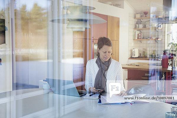 Schweden  Reife Frau beim Lesen von Dokumenten