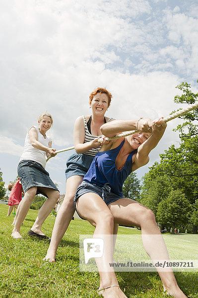 Schweden  Ostergotland  Frauen beim Tauziehen auf Rasen