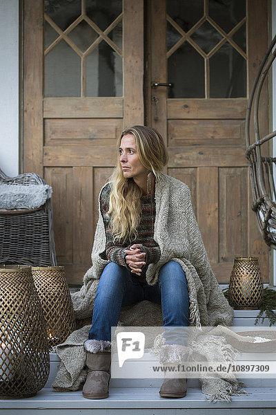 Schweden  Blonde Frau in Karo gehüllt auf der Veranda sitzend