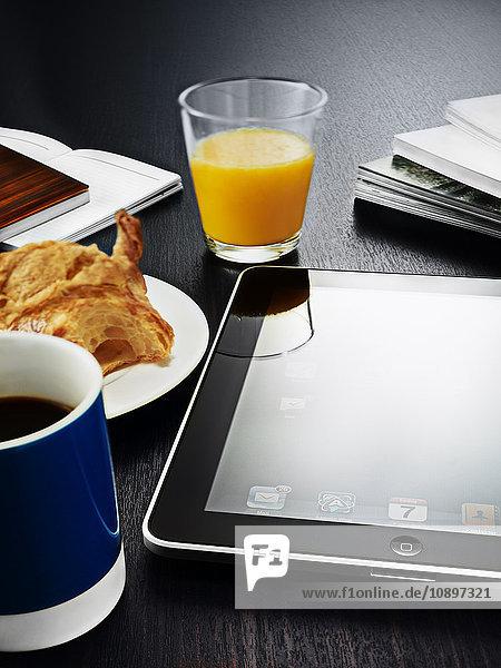 Digitales Tablett  Glas Orangensaft  Kaffee und Croissant auf dem Tisch