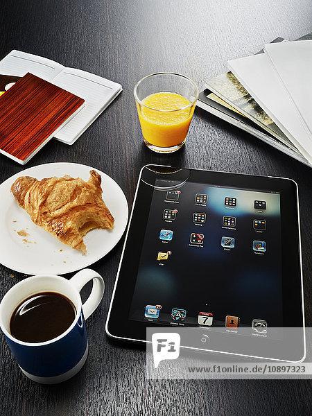 Digitales Tablett  Kaffeetasse  Croissant und Notizblock auf dem Tisch
