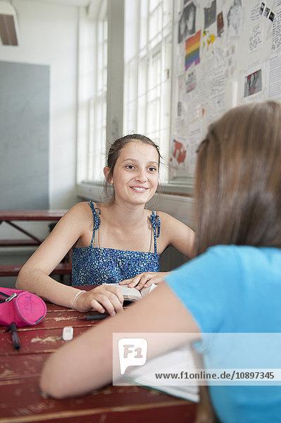 Zwei Mädchen (14-15) am Tisch sitzend  studierend