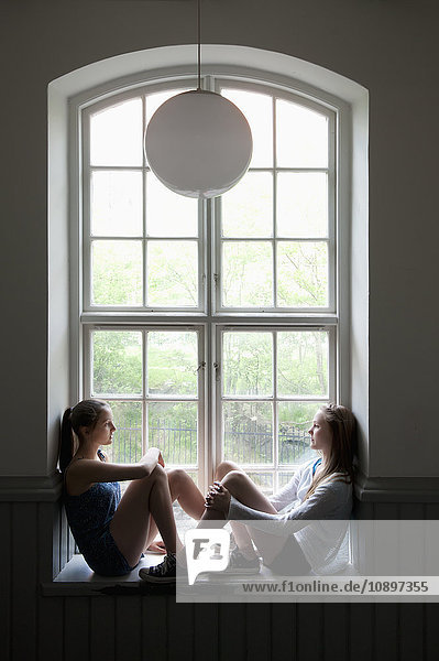 Zwei Mädchen (14-15) auf der Fensterbank sitzend