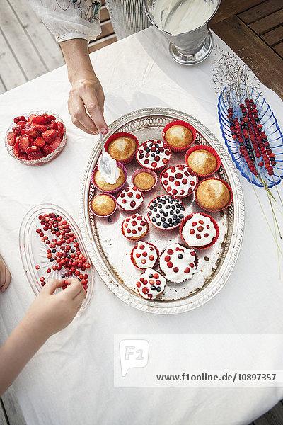 Schweden  Smaland  Mutter und Tochter (6-7) dekorieren Törtchen