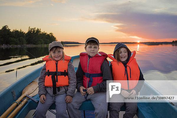 Schweden  Smaland  Tjust Archipel  Vastervik  Hasselo  Kinder (4-5  8-9  10-11) mit Schwimmwesten im Ruderboot bei Sonnenuntergang.