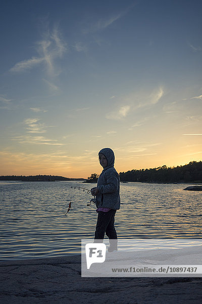 Schweden  Smaland  Tjust Archipel  Vastervik  Hasselo  Girl (4-5) Fliegenfischen am Seeufer bei Sonnenuntergang