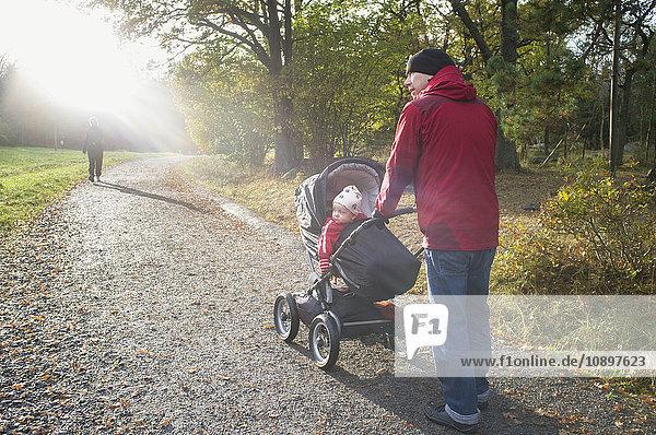 Schweden  Sodermanland  Nacka  Mann mit Sohn (12-17 Monate) zu Fuß im Park